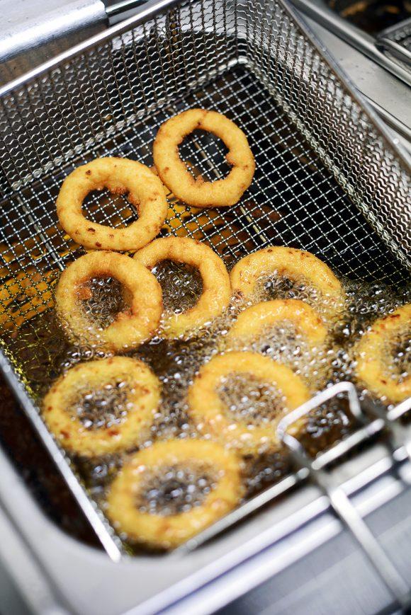 Golden battered onion rings frying in hot oil